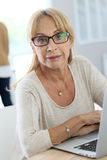 Elderly woman with eyeglasses using laptop Stock Photography
