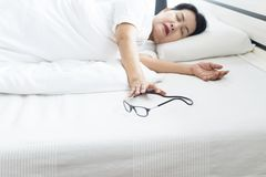 Elderly woman with eyesight problem hand searching or reach out eye glasses on bedroom royalty free stock photo