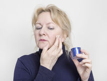 Elderly woman with face cream Royalty Free Stock Images