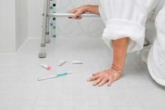 Elderly woman falling in bathroom Stock Image