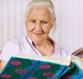 Elderly woman with a family album. Elderly woman looking at the family photo album Royalty Free Stock Photos