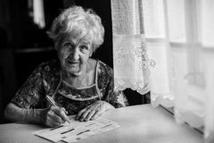 Elderly woman fills out a payment slip. Royalty Free Stock Photography