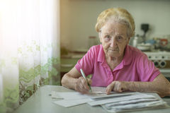An elderly woman fills out a receipt for payment of utilities, sitting in the kitchen Stock Photos