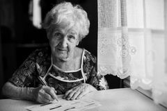 An elderly woman fills a receipt for payment of utility bills. Help. Stock Photography