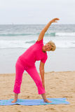 Elderly woman fitness. Happy elderly woman doing fitness working out on beach royalty free stock image