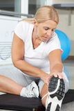 Elderly woman in fitness center. Stretching before training royalty free stock photos