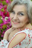 Elderly woman with flowers Stock Photos