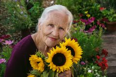 Elderly woman with flowers Royalty Free Stock Images