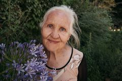 Elderly woman with flowers. Portrait of the smiling elderly woman with flowers, mother day royalty free stock image