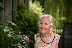 Elderly woman with flowers. Portrait of the smiling elderly woman outdoor in the garden with flowers, mother day stock images