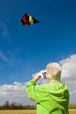 Elderly woman flying a kite. Elderly woman playing with a kite staying active Stock Photo