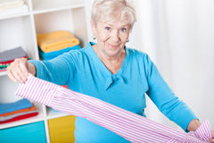 Elderly woman during folding laundry. At home royalty free stock photo