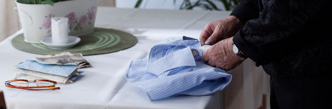 Elderly woman folding men's shirt Stock Image