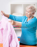Elderly woman folding shirt. Elderly woman folding striped shirt after ironing royalty free stock photo