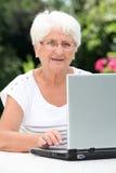Elderly woman in garden Stock Photography