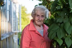 Elderly woman in the garden of his house. Elderly woman in the garden of his village house royalty free stock image