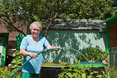 An elderly woman in the garden with water Stock Images