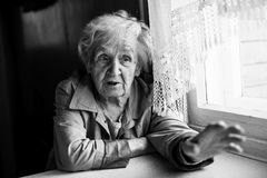 Elderly woman gesturing with hands while sitting at the table. Stock Photos