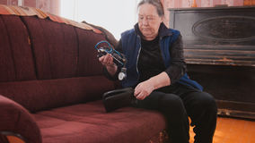 An elderly woman gets out of the case a device for measuring blood pressure Stock Photography