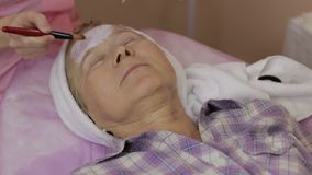 Elderly woman getting facial mask at spa salon stock footage