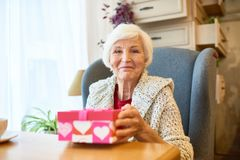 Elderly Woman with Gift Box. Portrait of happy senior woman holding gift box and looking at camera sitting in big armchair Royalty Free Stock Photo
