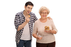 Elderly woman giving cookies to a young man Stock Photo