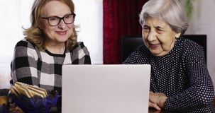 An elderly woman with glasses and a grandmother with deep wrinkles are looking at pictures on a laptop. Funny senior women smiling. Technology stock video