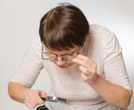 Elderly woman with glasses and magnifying glass Royalty Free Stock Image