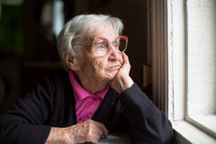 Elderly woman in glasses thoughtfully looking out the window. Loneliness. Royalty Free Stock Images