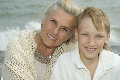 Elderly woman with grandson on beach Stock Photo