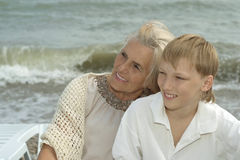 Elderly woman with grandson on beach Stock Images