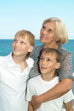 Elderly woman with grandsons on beach Royalty Free Stock Photos