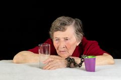 An elderly woman with gray hair looks longingly at the glassware. The woman`s hand is chained to a plastic Cup as a concept of stock photography