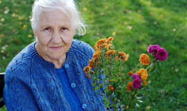 Elderly woman on green meadow Royalty Free Stock Image