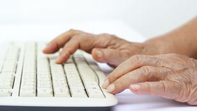 Elderly woman hands on computer keyboard stock footage