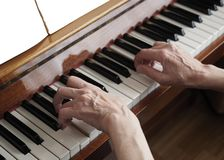 Elderly woman hands playing the piano, close up stock image