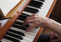 Elderly woman hands playing the piano, close up royalty free stock photos