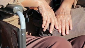 Elderly woman hands on a wheelchair.