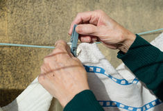 Elderly woman hanging clothes, hands detail Royalty Free Stock Images