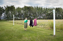 Elderly woman hanging clothes on the line outside. Stock Images