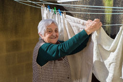 Elderly woman hanging out the washing on the terrace Stock Images