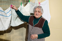 Elderly woman hanging out the washing Royalty Free Stock Photography