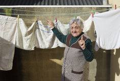 Elderly woman hanging out the washing Royalty Free Stock Photos