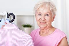 Elderly woman hanging shirt on hanger Stock Image
