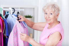Elderly woman hanging shirt Stock Image