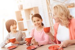 Elderly woman and happy grandson and granddaughter drink tea from red mugs in kitchen. Elderly women and happy grandson and granddaughter drink tea from red royalty free stock photo