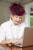 Elderly woman in a hat using laptop computer Royalty Free Stock Photo