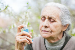 Elderly woman having asthma attack, holding a bronchodilator Royalty Free Stock Photo