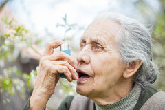 Elderly woman having asthma attack, holding a bronchodilator Royalty Free Stock Image