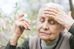 Elderly woman having asthma attack, holding a bronchodilator Royalty Free Stock Photos